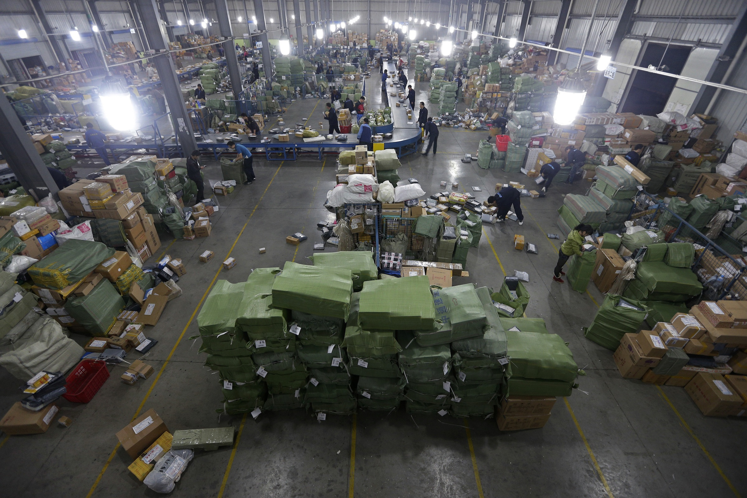 A general view shows employees sorting packages along a conveyor belt at a hub of ZTO Express Delivery company in Wuhan